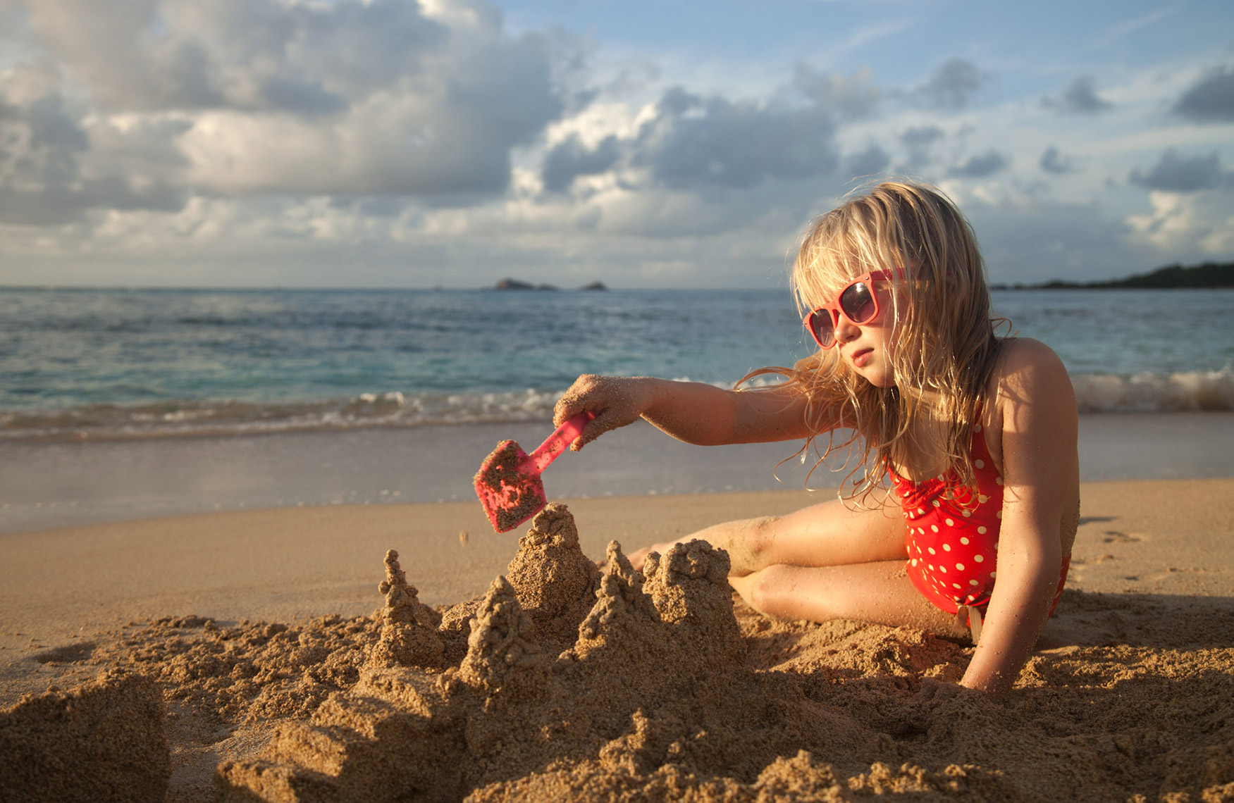 A-YOUNG-GIRL-BUILDING-A-SANDCASTLE-ON-THE-BEACH