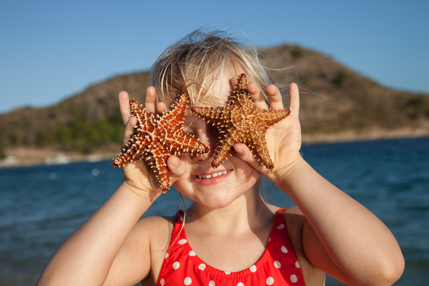 A-YOUNG-GIRL-HOLDING-STARFISH-OVER-HER-EYES