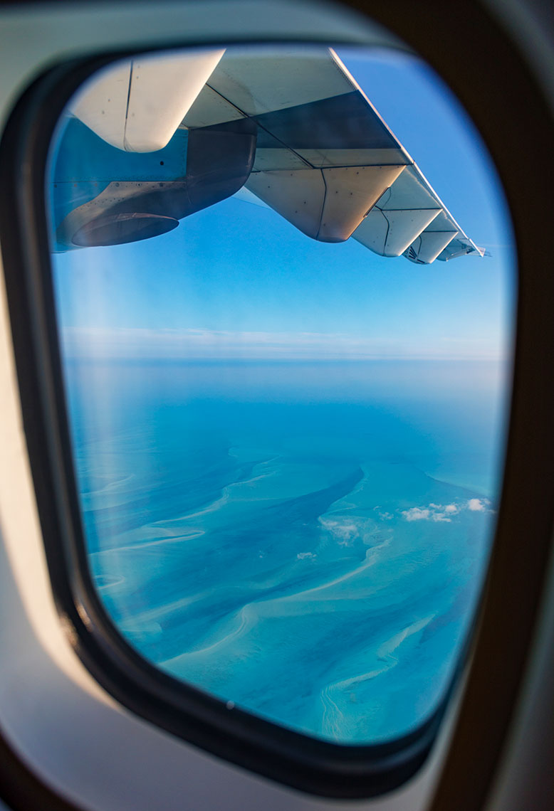 AIRPLANE-WINDOW-AND-BAHAMAS-WATERS