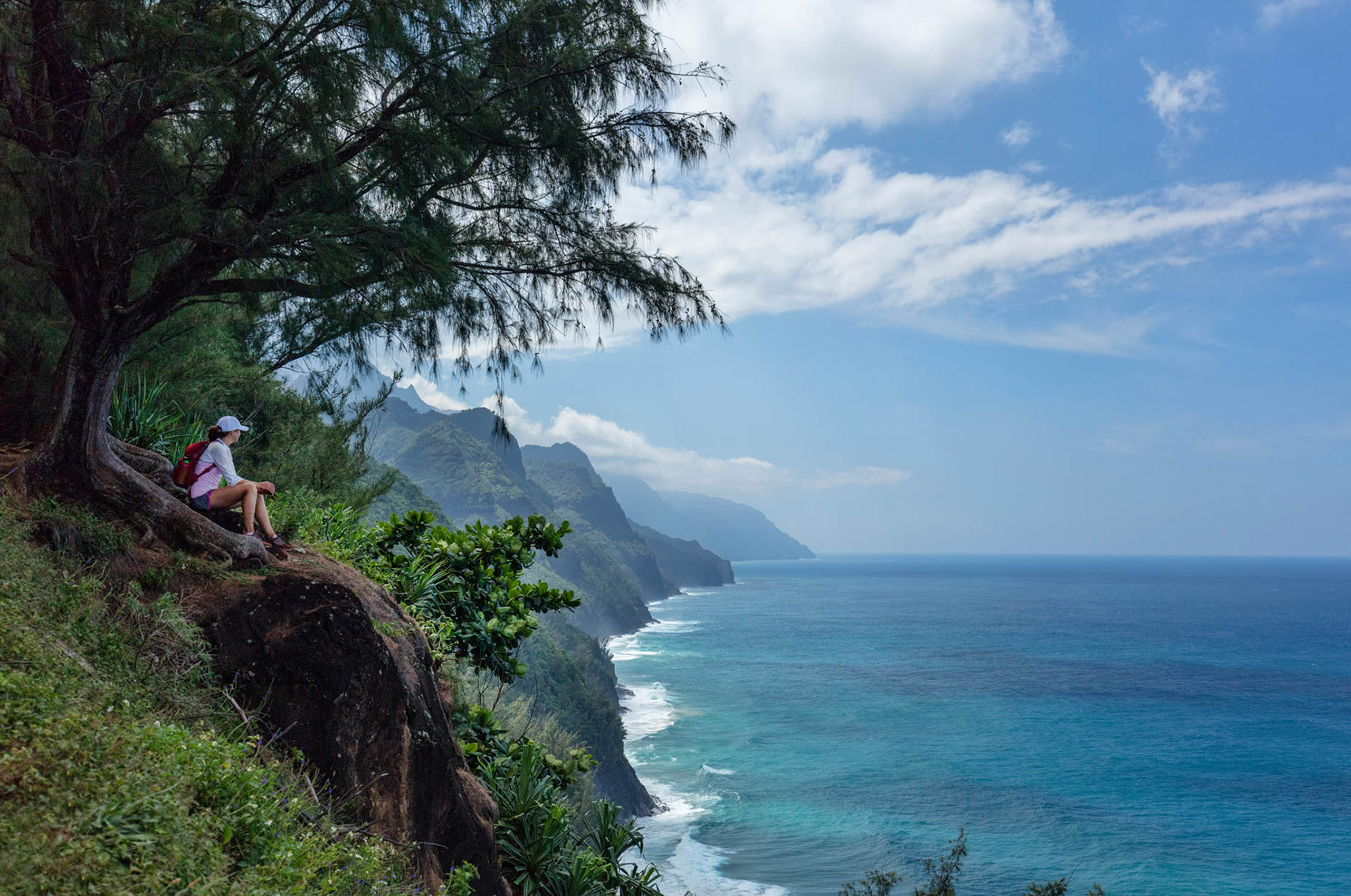 female-hiker-taking-in-Na-Pali-Coast-view_Kauai_Hawaii